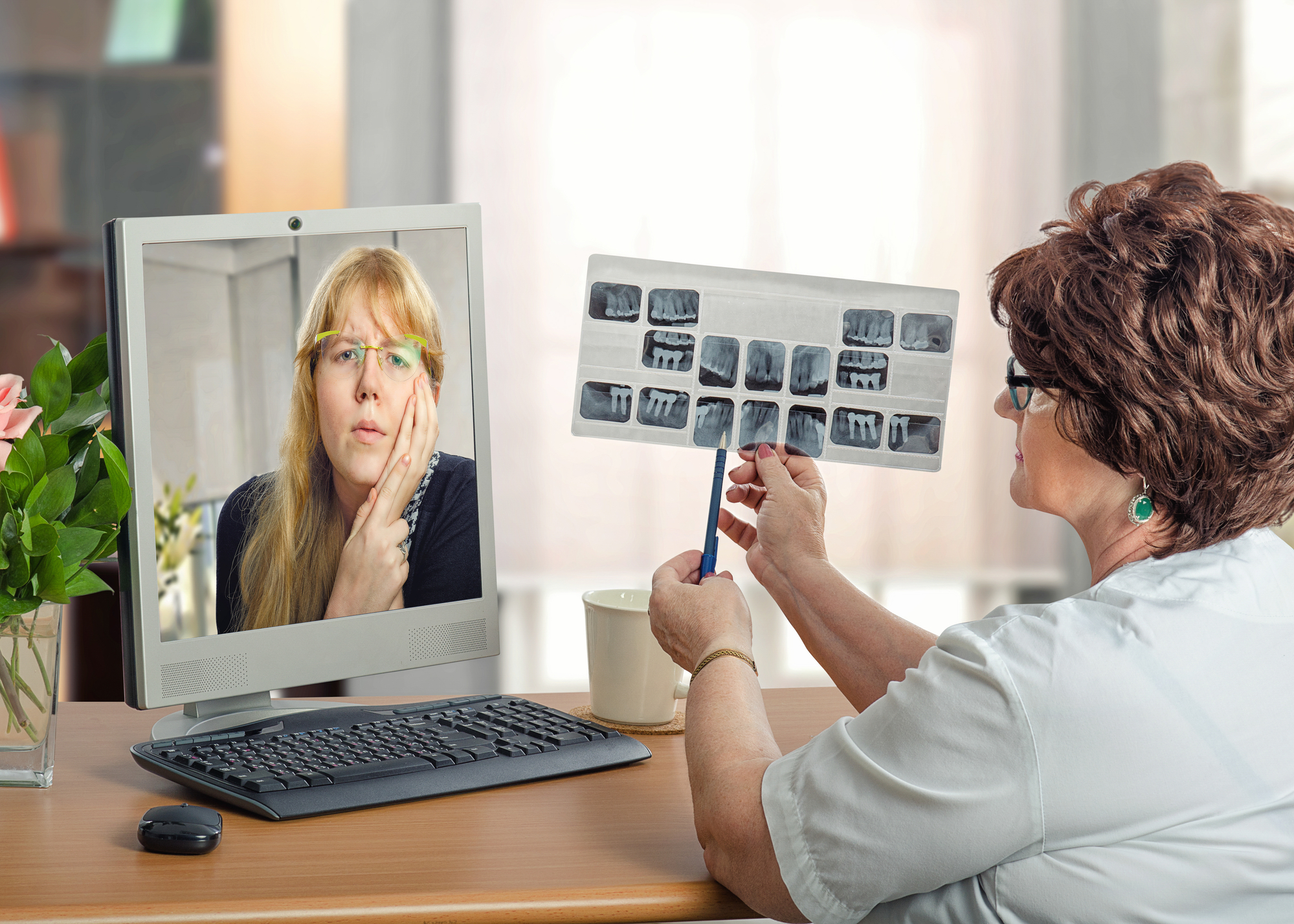 dentist performing teledentistry appointment with patient